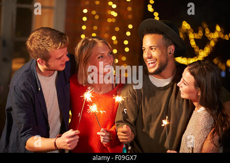 Group Of Friends Lighting Sparklers At Outdoor Party - Stock Photo