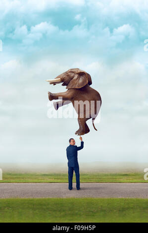 business strength concept businessman holding an elephant with one finger - Stock Photo
