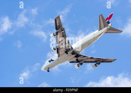 MK transport Boeing 747 flaying overhead with its wheels down while making approach to local airport. Blue and white - Stock Photo