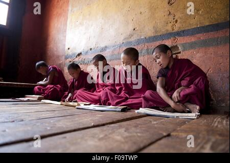 Young monks sitting in prayer hall of Paro Dzong monastery and reading prayer, Bhutan - Stock Photo