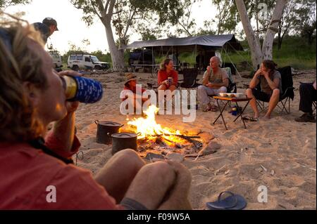 People sitting around camp fire in Ormiston Creek, Alice Springs, Australia - Stock Photo