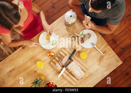 Top view of couple enjoying a healthy morning breakfast in kitchen at home. Breakfast table with loaf of bread, - Stock Photo