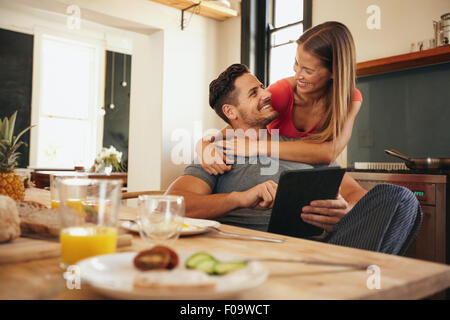 Shot of loving young couple in kitchen by breakfast table in morning. Man using digital table while woman hugging - Stock Photo