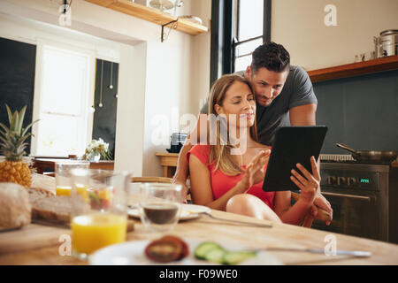 Young couple in kitchen looking at tablet pc. Man standing by his girlfriend sitting using digital tablet in morning. - Stock Photo