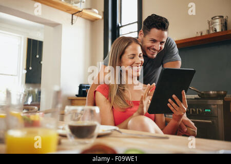 Happy young couple in the modern kitchen in the morning, using a digital tablet. Smiling young woman showing something - Stock Photo