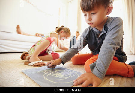 Little boy drawing and coloring while sitting on floor in living room. Children on floor painting with parents sitting - Stock Photo