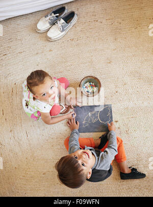 Top view of two little kids sitting on floor looking up at camera while drawing. - Stock Photo