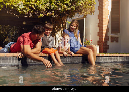 Portrait of young family with two children relaxing by their swimming pool having fun. Parents with kids sitting - Stock Photo