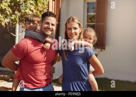 Outdoor shot of a happy couple carrying their children on their backs. Portrait of a mother and father giving their - Stock Photo