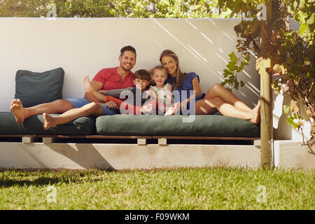Portrait of happy young family sitting on patio smiling at camera. Couple with kids sitting on couch in their backyard. Stock Photo