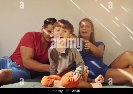 Happy little boy sitting on patio with his family at the back. Focus on little boy sitting in front with his parents - Stock Photo