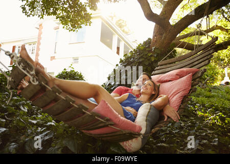 Portrait of an affectionate young couple lying on a hammock looking away smiling. Romantic young man and woman on - Stock Photo