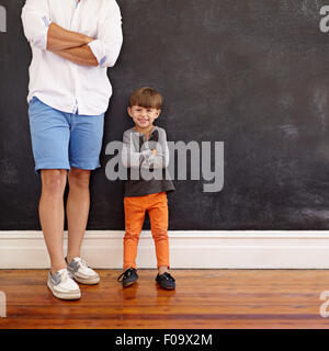 Indoor shot of little boy standing next to his father with hands folded and smiling.  Cropped shot of young man - Stock Photo