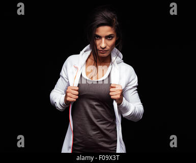Young woman looking at camera with an attitude. Fitness female model in sportswear on black background - Stock Photo