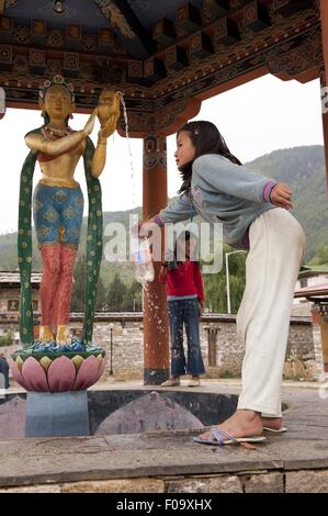Girls filling water in bottle at Memorial Chorten in Thimphu, Bhutan - Stock Photo