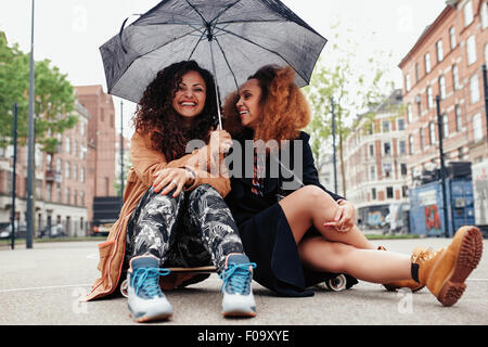 Two female friends sitting together on skateboard. Smiling young women outdoors on city street with umbrella. - Stock Photo
