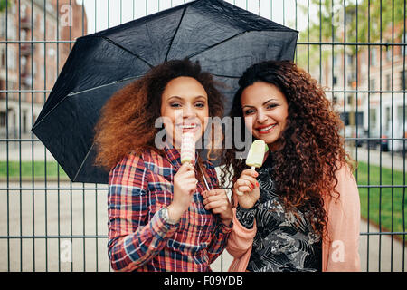 Portrait of two young women standing under umbrella eating an ice cream. Happy young female friends outdoor. - Stock Photo