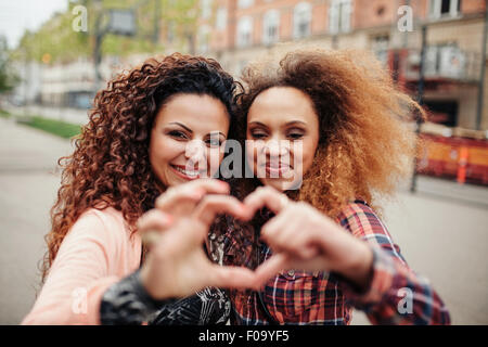 Beautiful young women making heart shape with fingers. Two women standing together outdoors on city street. - Stock Photo
