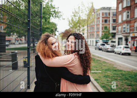 Outdoor shot of two girlfriends walking through town looking over shoulder smiling. Happy young women walking together - Stock Photo