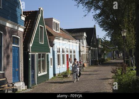 Woman cycling on road beside old captain's houses in Buiksloterdijk, Noord, Amsterdam - Stock Photo