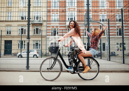Portrait of two happy young women enjoying bike ride on city street. Female friends riding on one bicycle. - Stock Photo