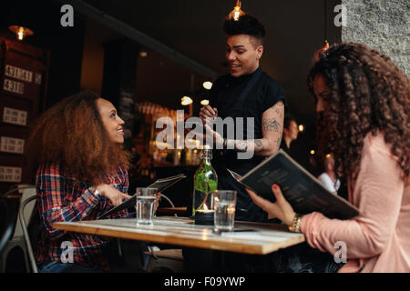 Young woman with a friend ordering to waiter holding digital tablet. Two women sitting at cafe holding menu card - Stock Photo