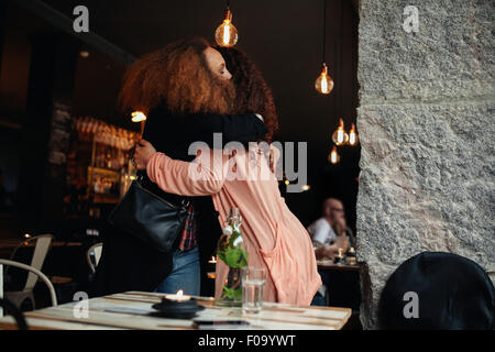 Two young women meeting at a restaurant. Friends hugging each other at a cafe. - Stock Photo