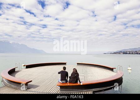 People sitting on bench at Lake Geneva, Montreux, Riviera-Pays-d'Enhaut, Canton of Vaud - Stock Photo
