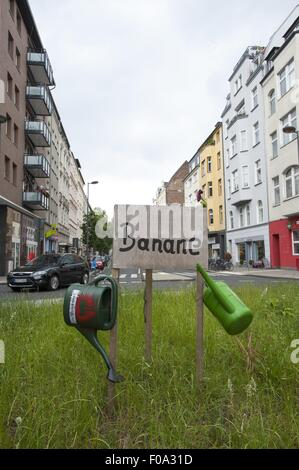 Watering cans hanged on sign board of Banane on Bonner Street, Southtown, Cologne, Germany - Stock Photo