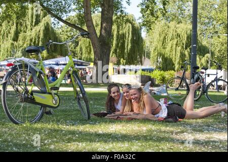 Three women relaxing in front of bicycle in Aachener Weiher, Cologne, Germany - Stock Photo
