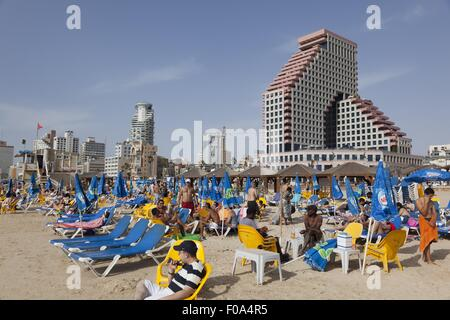 Tourists relaxing on sun lounger on beach near Allenby Street, Tel Aviv, Israel - Stock Photo