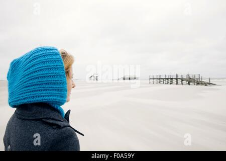 Contemplative blonde woman wearing coat and blue cap on beach, smiling - Stock Photo