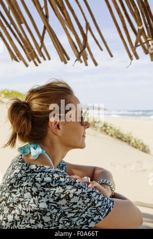 Side view of woman sitting on beach, Maputaland Marine Reserve, South Africa - Stock Photo