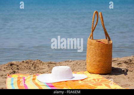 Several beach accessories, bag, hat and color towel put on the sand close to the sea water. It is the middle of - Stock Photo