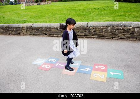 Girl playing hopscotch in playground - Stock Photo
