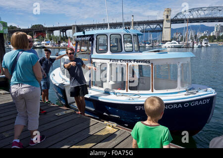 People on Granville Island getting ready to board a False Creek ferry boat which tours around False Creek in Vancouver, - Stock Photo