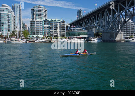 Two woman kayaking in False Creek in Vancouver, by Granville Bridge.  Yaletown condo towers along the waterfront. - Stock Photo