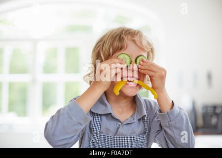 Boy playing with vegetables in kitchen - Stock Photo