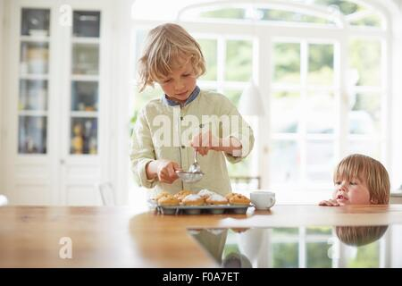 Boys making cupcakes in kitchen - Stock Photo