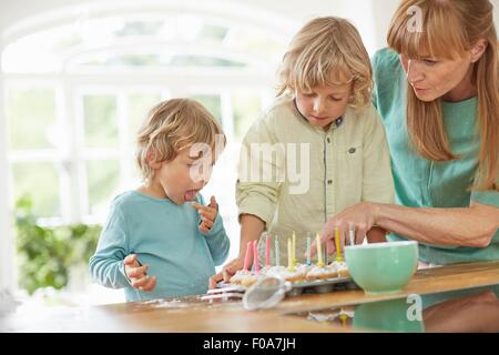Mother and sons making cupcakes in kitchen - Stock Photo