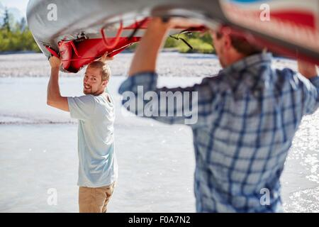Rear view of two men carrying dinghy above their heads to water - Stock Photo
