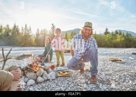 Mid adult man crouching next to campfire wearing hat, looking at camera, smiling - Stock Photo