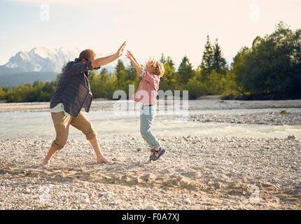 Side view of young man and boy jumping, doing high five, Wallgau, Bavaria, Germany - Stock Photo