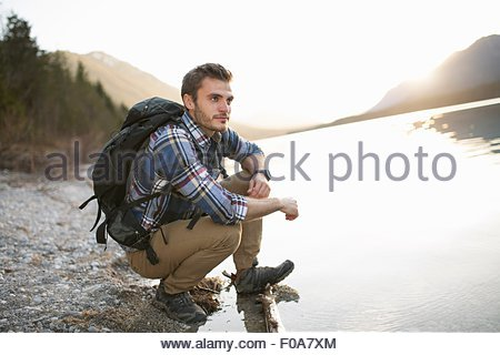Young man, hiking, crouching by lake, taking in the view - Stock Photo