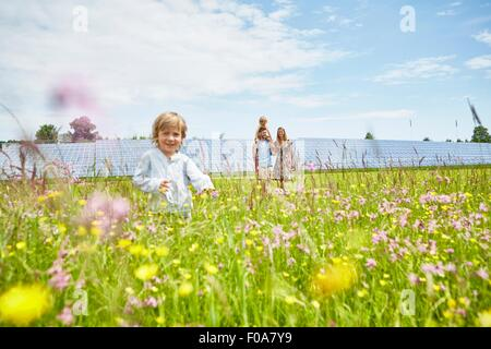 Young boy running through field, mother, father and brother following behind, next to solar farm - Stock Photo