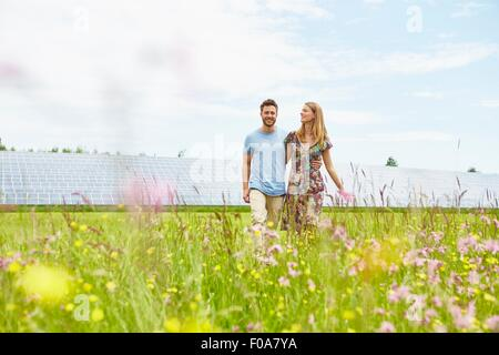 Young couple walking through field next to solar farm - Stock Photo