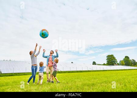 Young family playing with inflatable ball, on field, next to solar farm - Stock Photo
