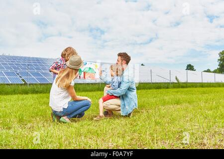Young family sitting in field, looking at child's drawing of house, next to solar farm - Stock Photo