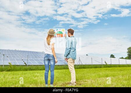 Young couple standing in field, looking at child's drawing of house, next to solar farm - Stock Photo