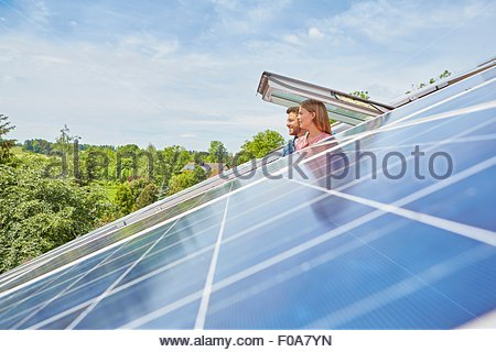 Young couple looking out of window of solar panelled roof - Stock Photo